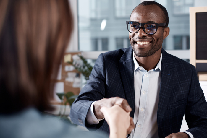 young man shaking hands during job interview